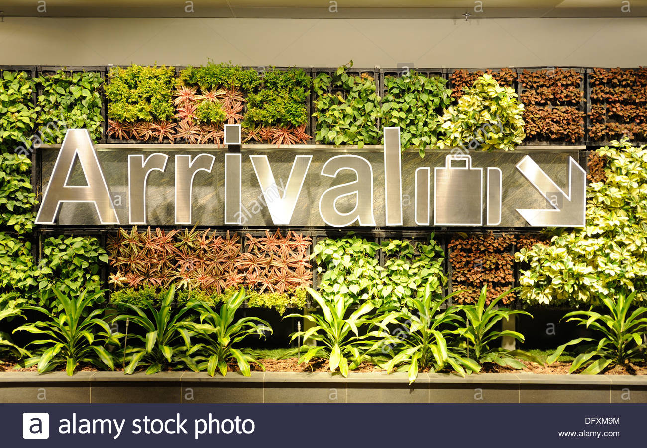 Singapore - Changi Airport. Directions for arrivals to the baggage claim, surrounded by a living wall. - Stock Image