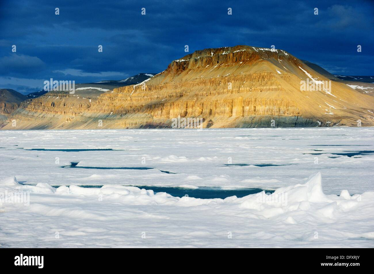 Midnight sun light over icepack and cliffs in spring, Arctic Bay, Baffin Island, Nunavut, Canada - Stock Image