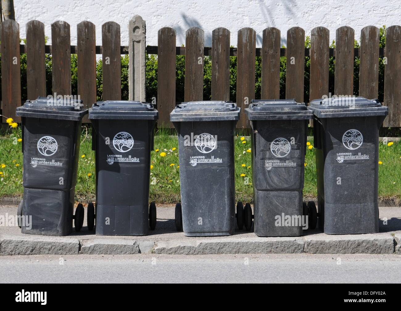 Five trash cans on the roadside - Stock Image