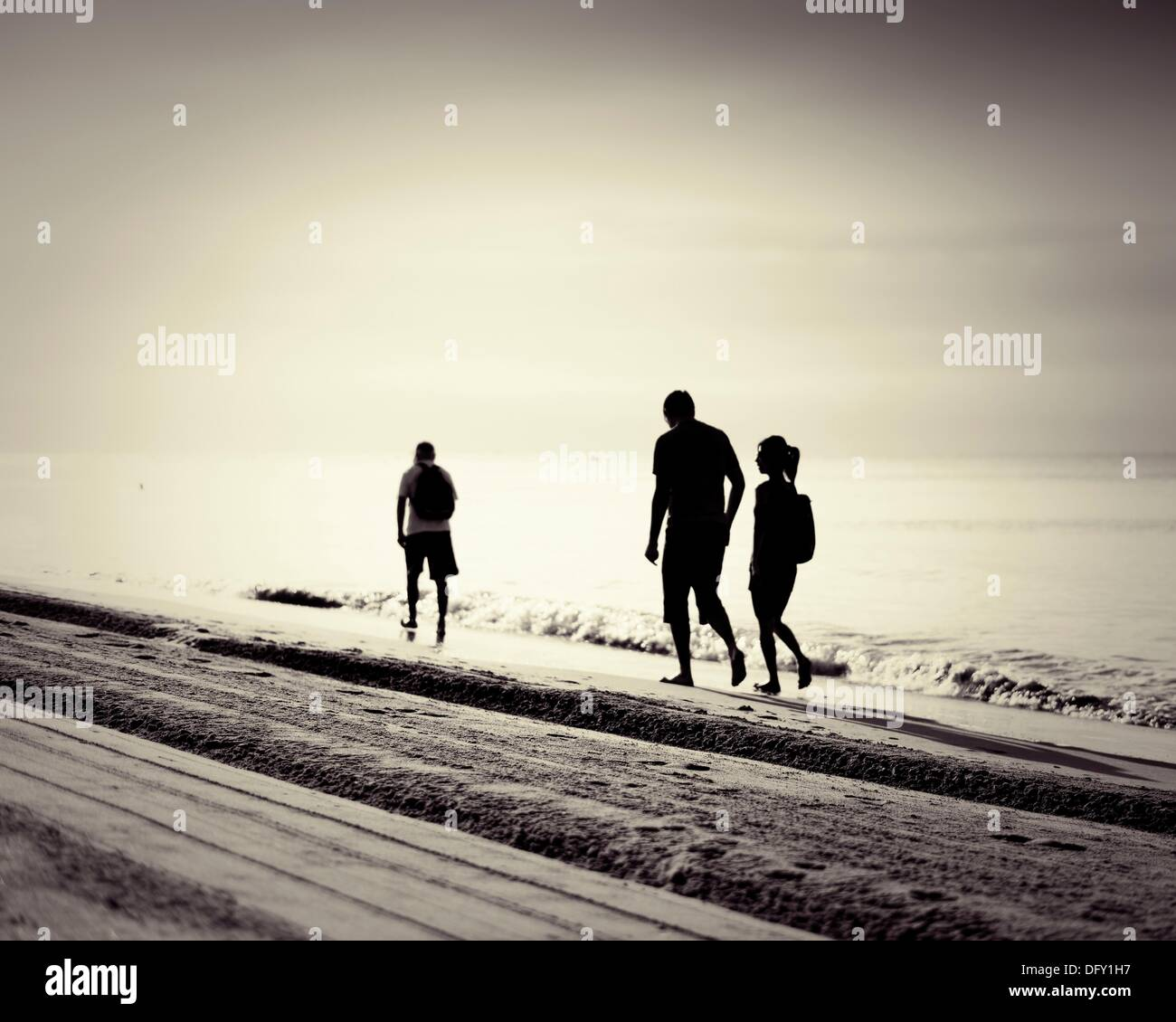 Walkers along the sea at dawn  Mediterranean Sea  Costa Dorada  Spain - Stock Image