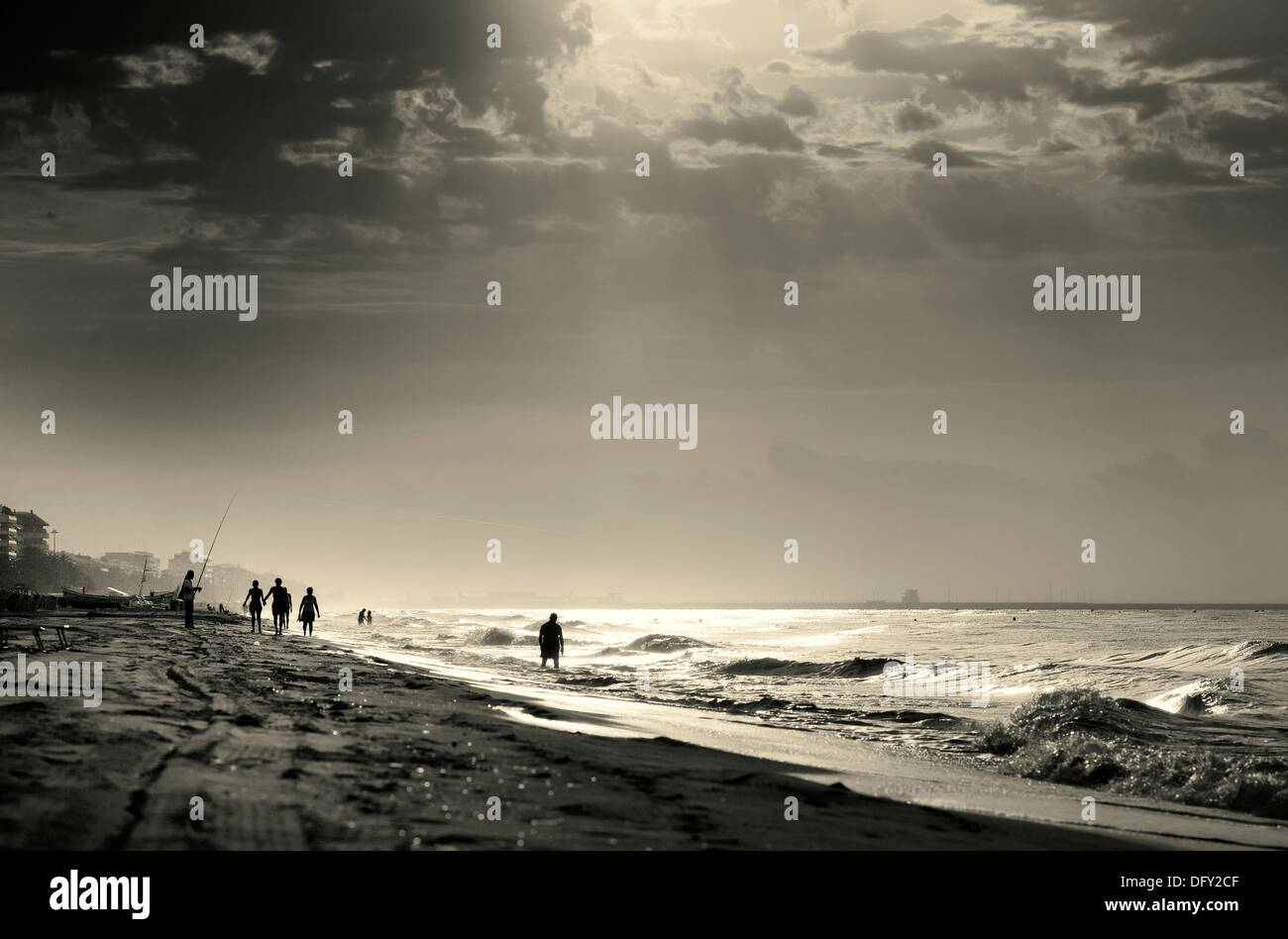 People walking along the sea at dawn Mediterranean Sea - Stock Image