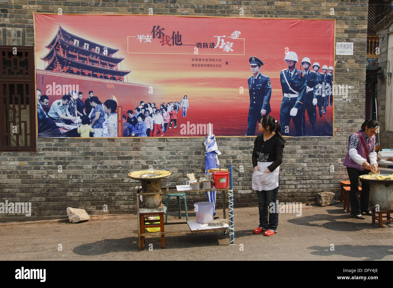 government propaganda mural over street vendor in Jianshui China - Stock Image