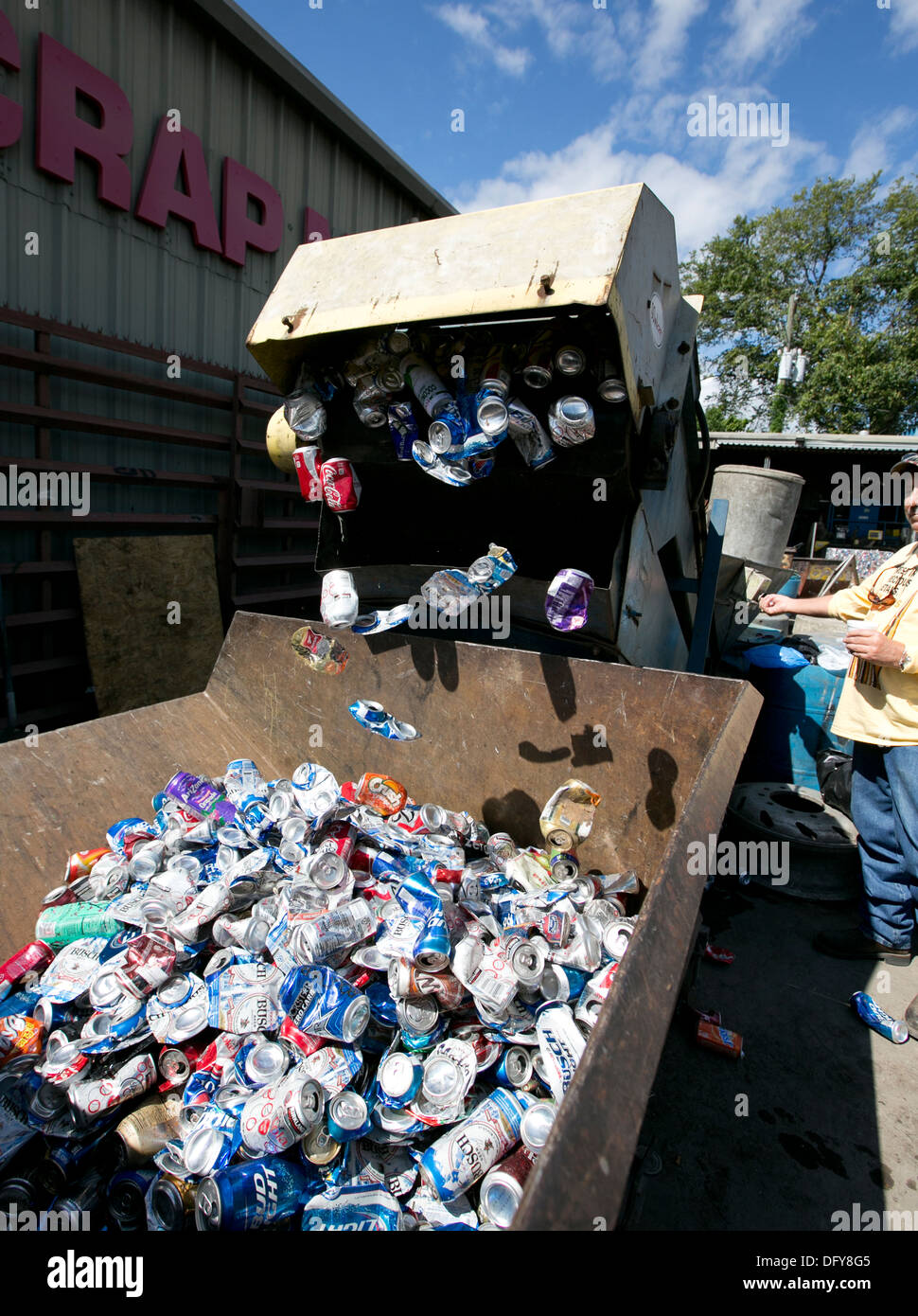 Male employee uses machine to crush aluminum cans at a metal recycling company in Texas - Stock Image