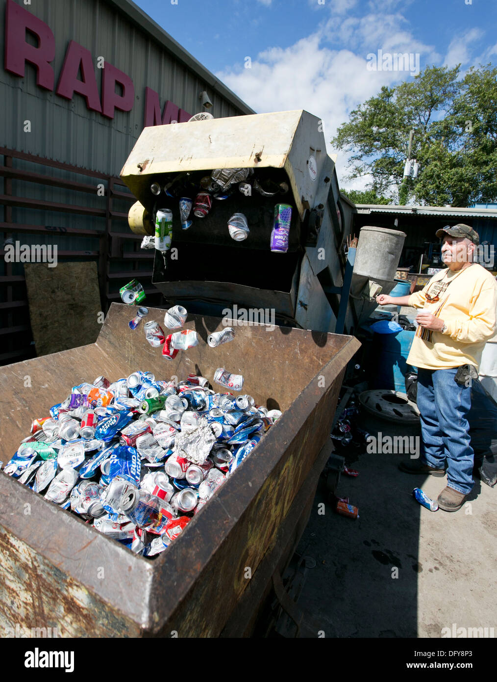 Male employee uses machine to crush aluminum cans at a metal recycling company in Texas Stock Photo