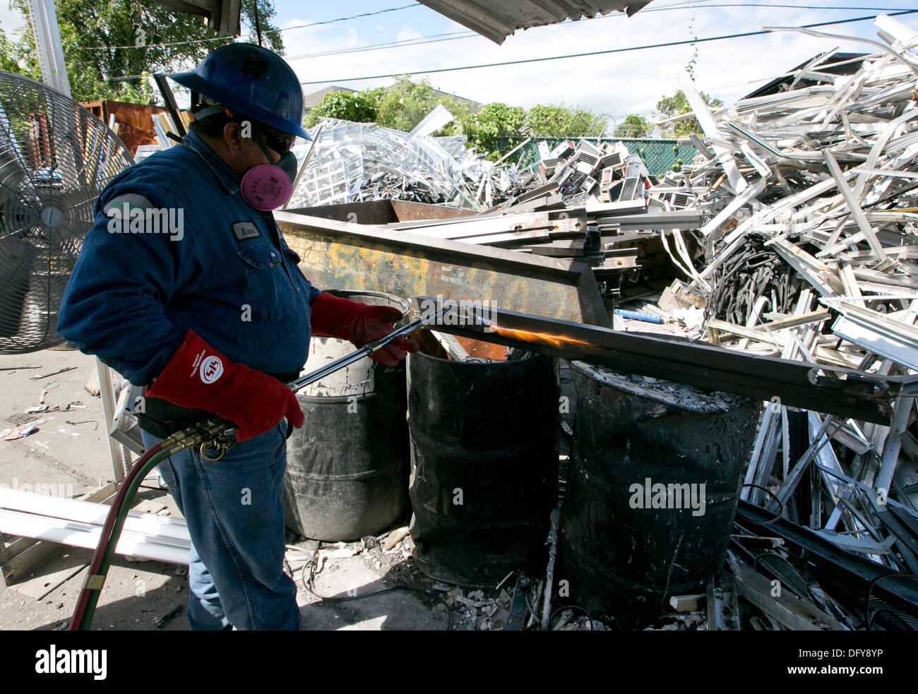 Male worker uses a blow torch to separate different types of metal for recycling at a scrap metal company in Texas - Stock Image