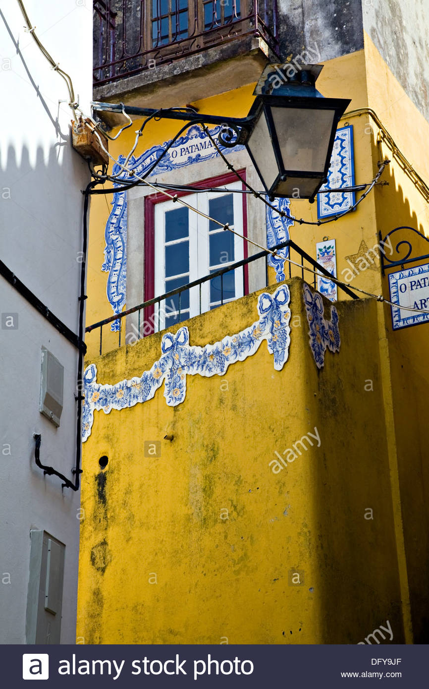 Yellow painted building with decorative wall tiles and street Stock ...