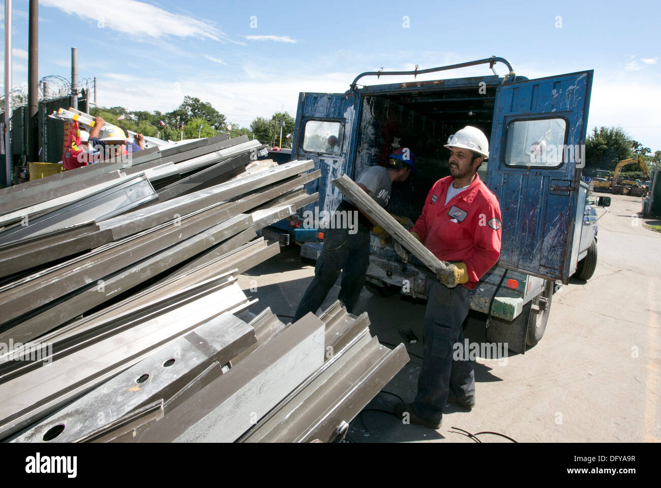 Hispanic male workers arrange metal beams for recycling at scrap metal company in Texas - Stock Image