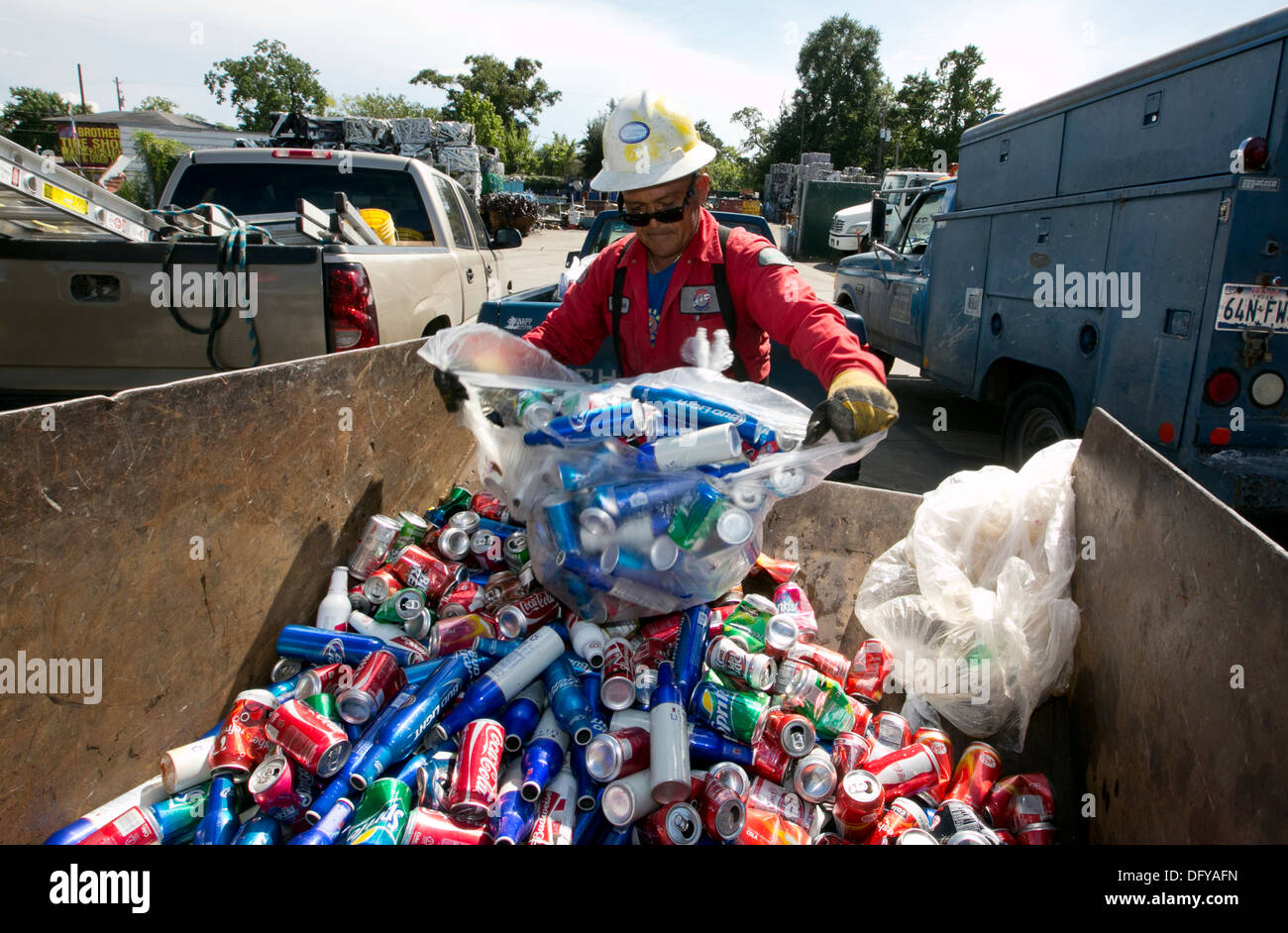Worker at scrap metal recycling plant empties bag of cans, beer cans, soda cans in Texas - Stock Image