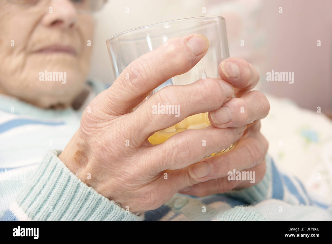 Elderly woman patient holding a glass with a drink of orange juice - Stock Image