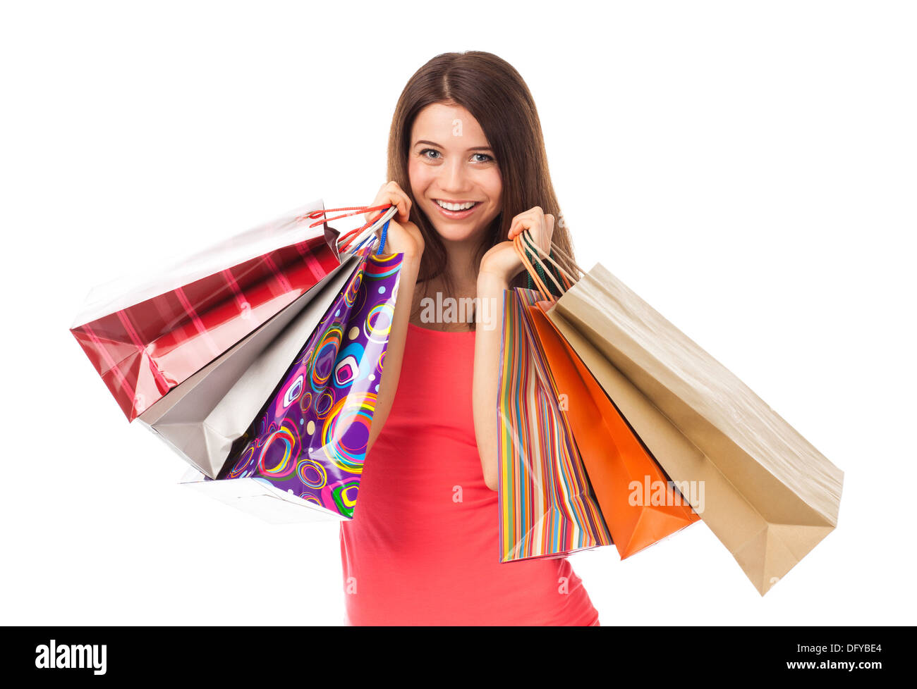 Portrait of a young woman holding shopping bags and smiling, isolated on white - Stock Image
