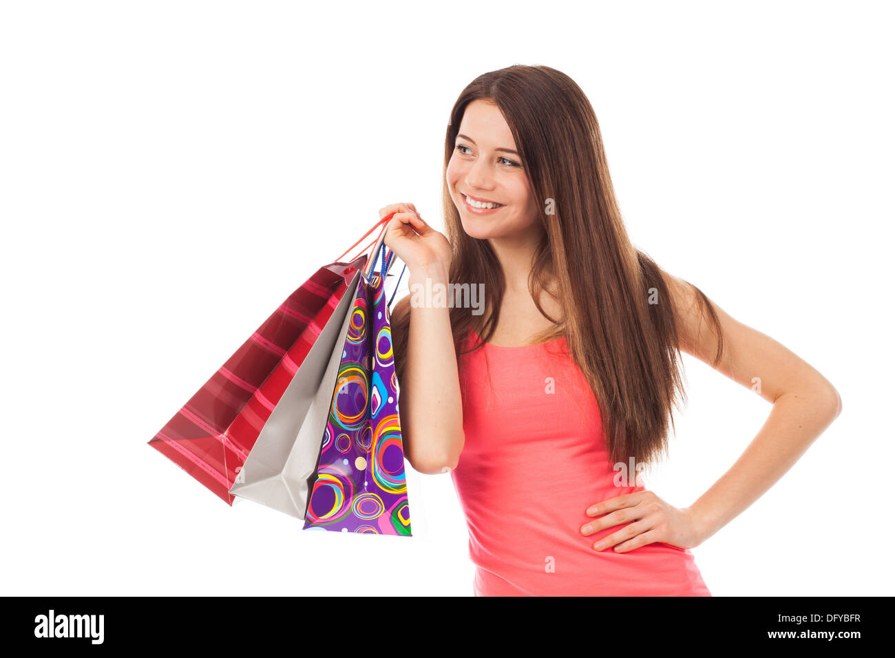 Nice brunette with a cute smile holding shopping bags, isolated on white - Stock Image