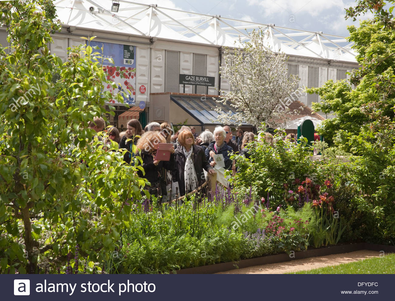 Visitors To The RHS Chelsea Flower Show Looking At A Garden On Main Avenue.  The Homebase Garden, Designer Adam Frost