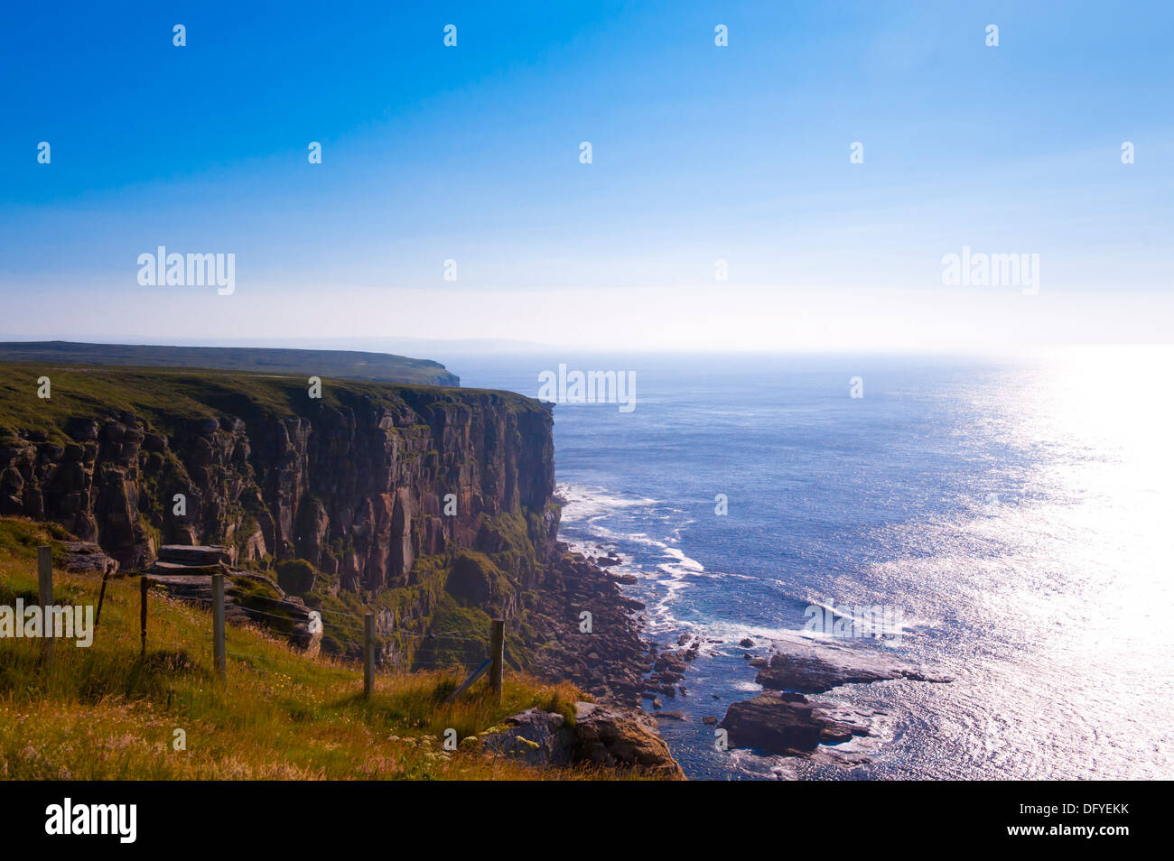 Cliffs at sea with strong sun reflecting on water - Stock Image