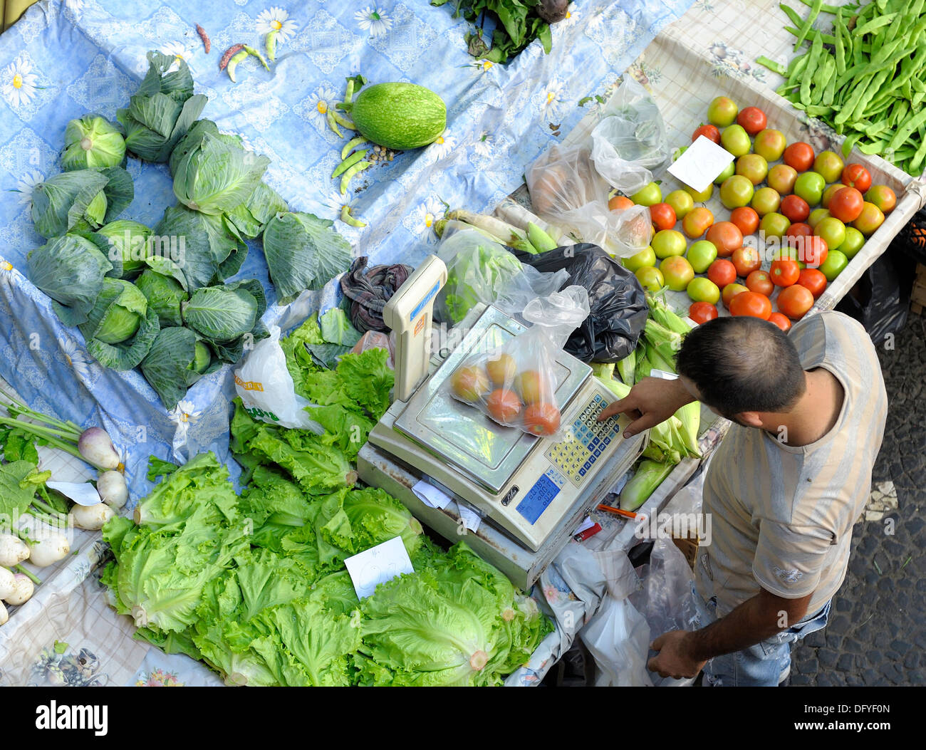 A man on a fruit and vegetable market stall using weighing scales Funchal Madeira Portugal - Stock Image