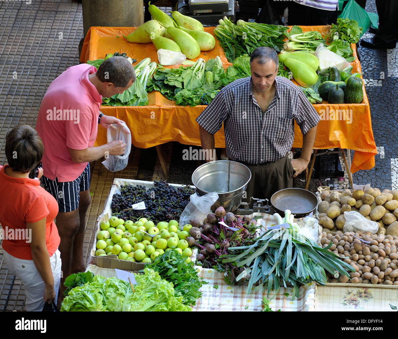 A man selecting black grapes on a fresh fruit and vegetable stall Funchal Madeira Portugal - Stock Image