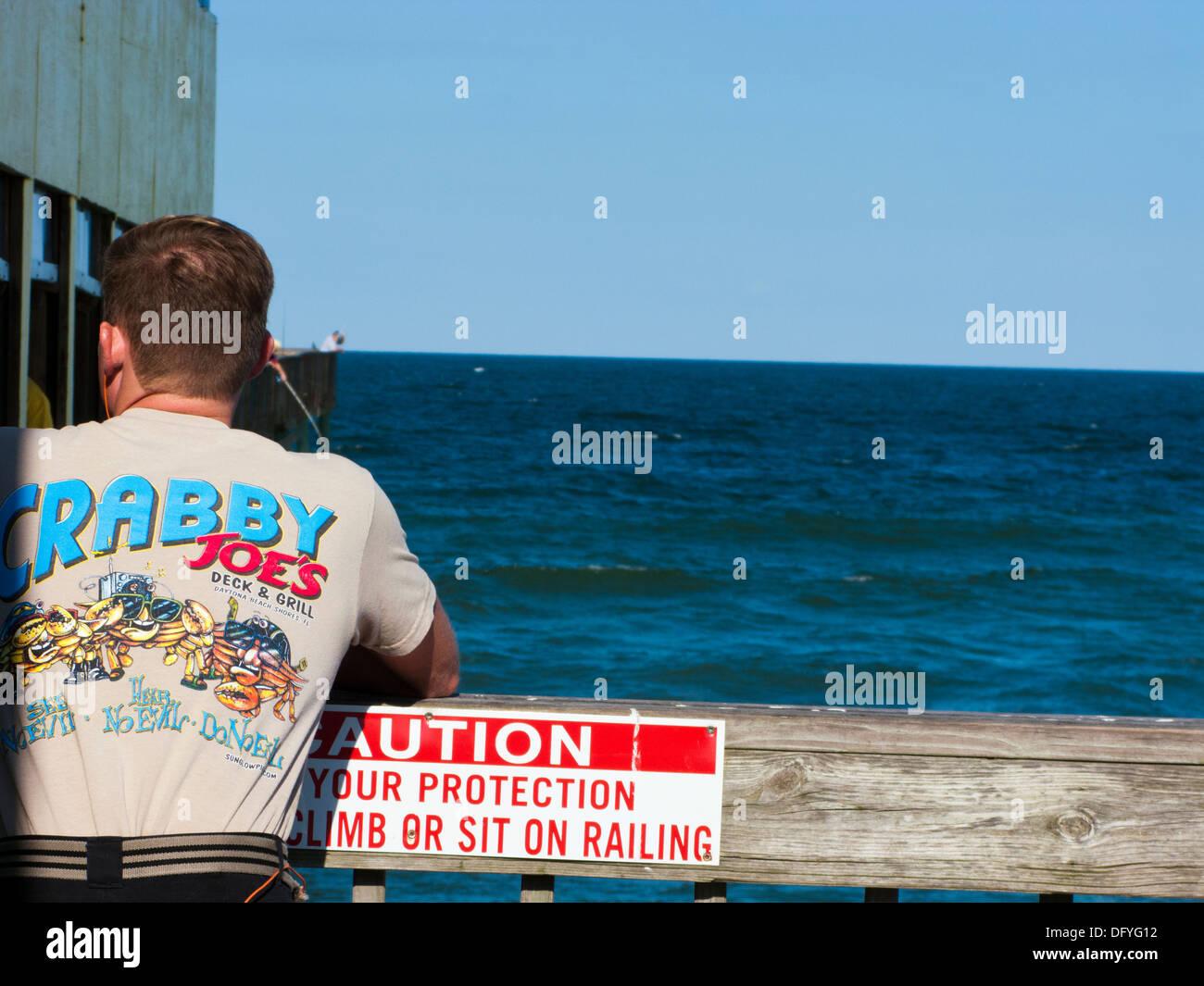 Man wearing Crabby Joe's T shirt on the pier in Daytona beach shores Stock Photo