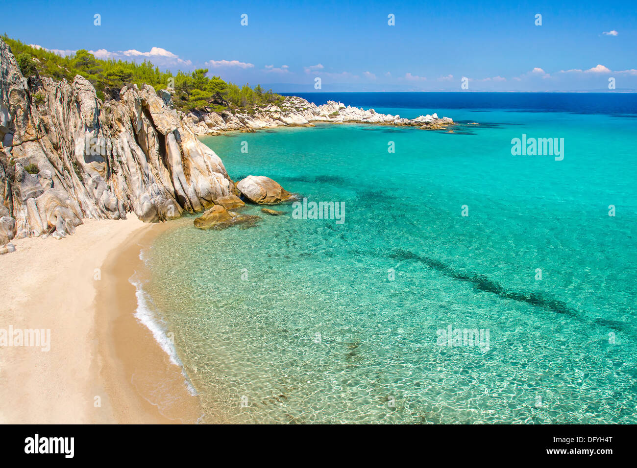 Rocky cliff above the beautiful clear water of the Aegean sea - Stock Image