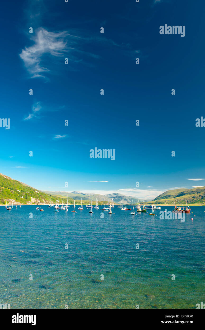 View across water with sailing boats in Ullapool harbour - Stock Image
