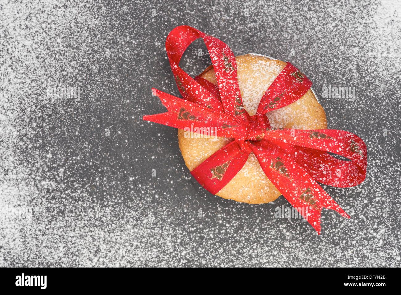 Sweet Christmas mince pie with a red ribbon tied round it on a Slate cooling board with icing sugar. - Stock Image