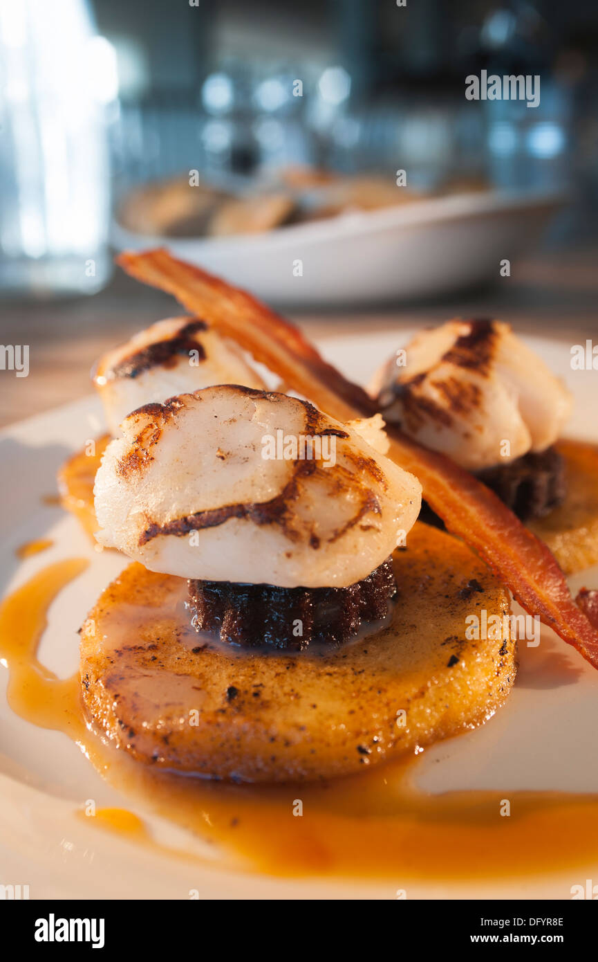 Scallops served with black pudding, on a base of English apples and with crisp prosciutto - Stock Image