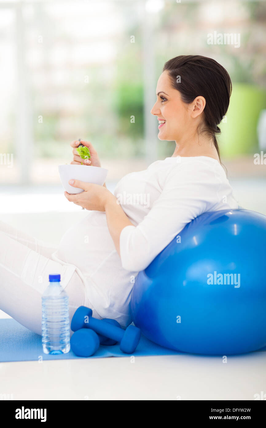 young pregnant woman holding bowl of green salad on exercise mat Stock Photo