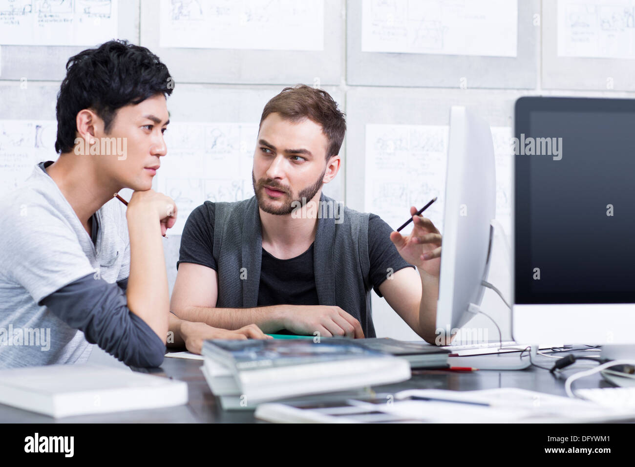 Young adults discussing in office - Stock Image