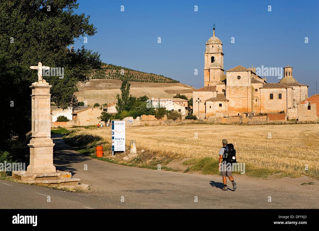 Pilgrim, cross and Colegiata de Santa María del Manzano.Castrojeriz. Burgos province. Spain. Camino de Santiago - Stock Image