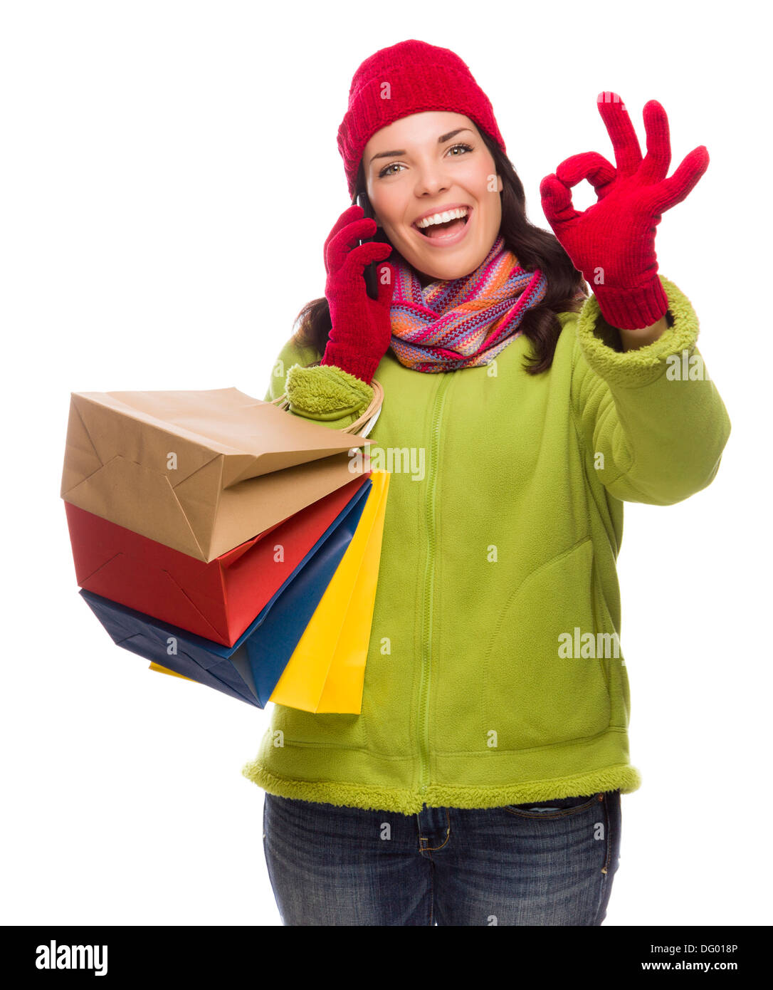 Mixed Race Woman Holding Shopping Bags Talking On Her Cell Phone Giving Ok Gesture Isolated on White Background. - Stock Image