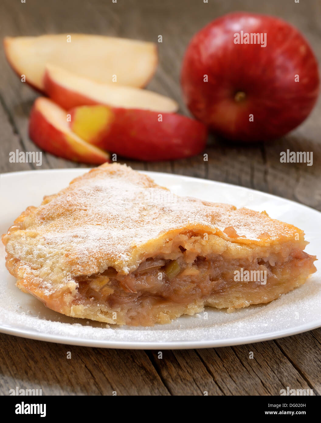 Apple pie on the white plate on wooden table - Stock Image