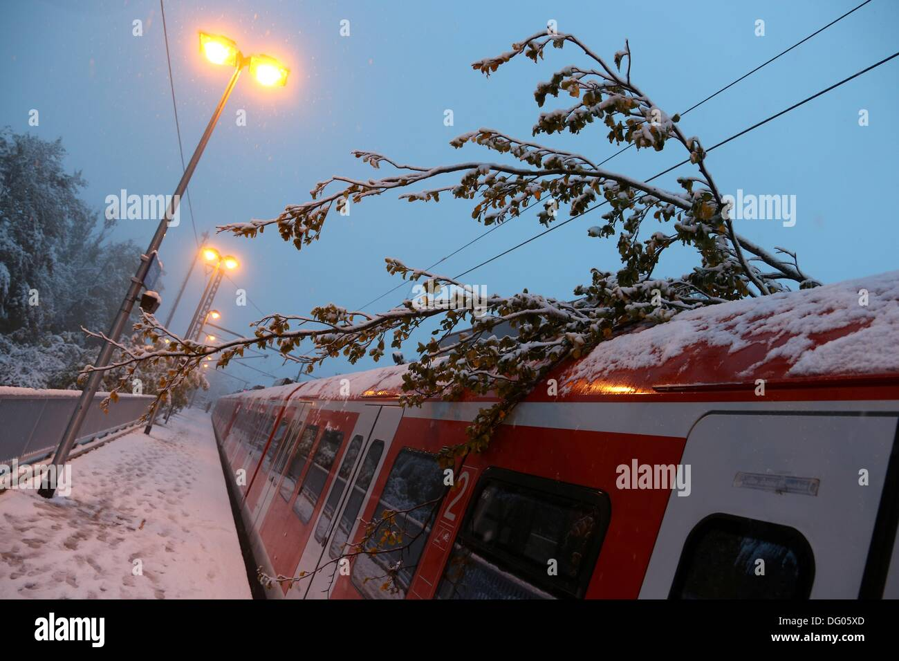 Icking, Germany. 11th Oct, 2013. Parts of a tree lie on top of an S-Bahn, which was halted in the station by heady snowfall in Icking, Germany, 11 October 2013. Heavy snow during the night in southern Bavaria caused many headaches with falling branches, train cancellations and school closures. Photo: STEPHAN JANSEN/dpa/Alamy Live News - Stock Image