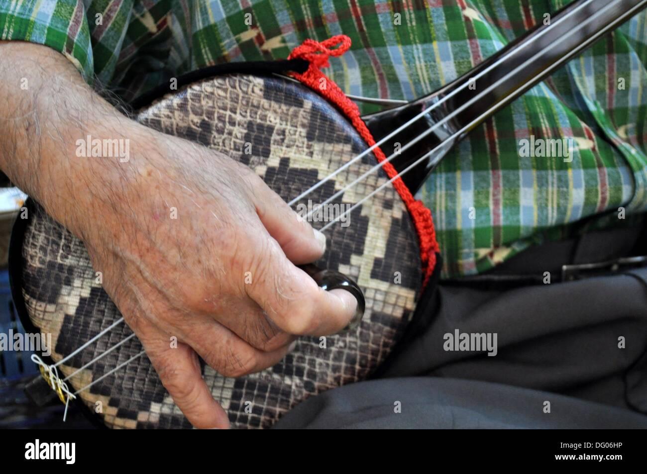 Naha Japan: man playing a Sanshin 3-stringed lute - Stock Image