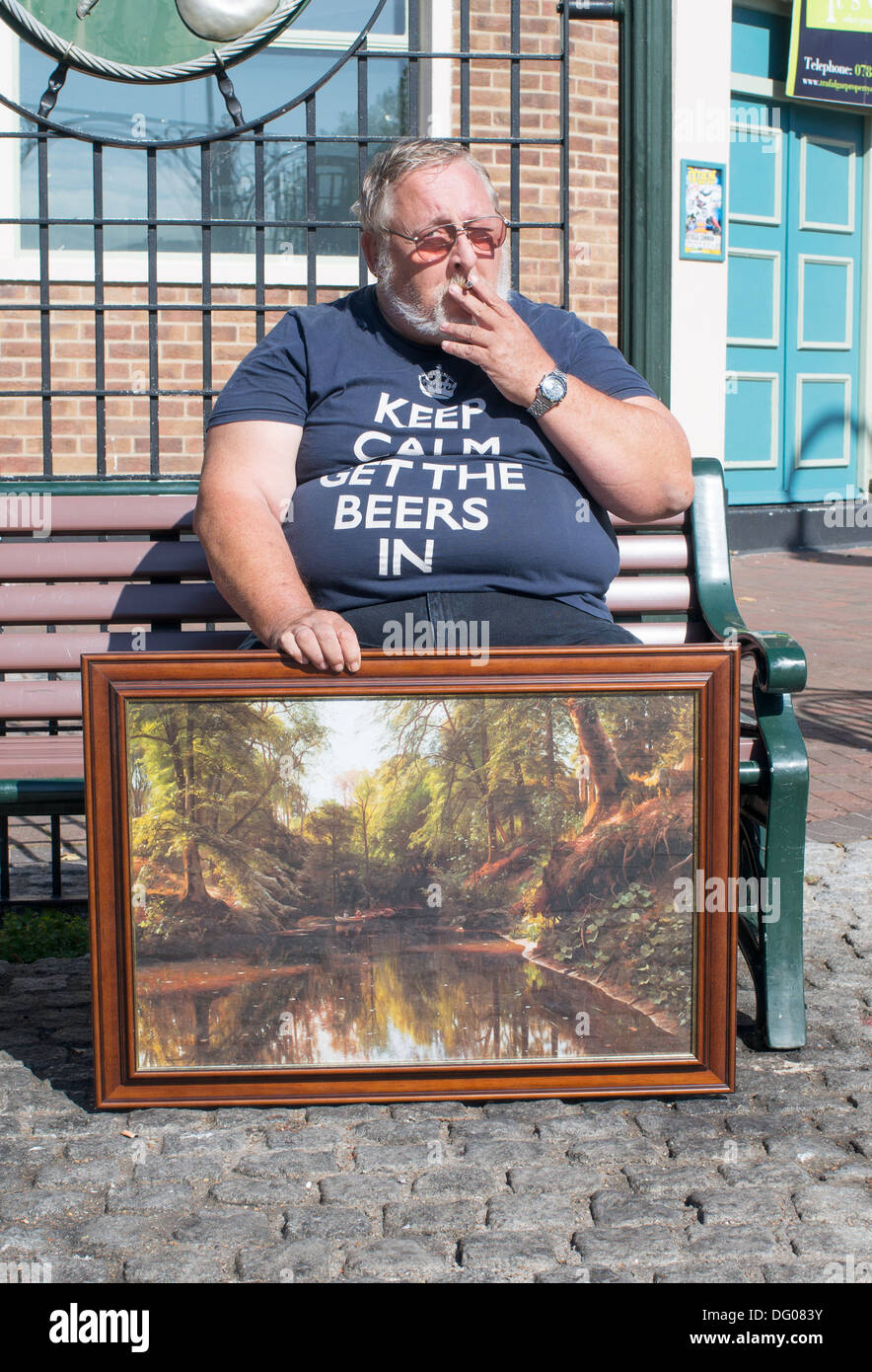 Obese man smoking and holding painting Gosport, Hampshire, England, UK Stock Photo
