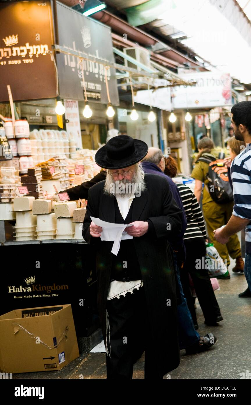 An Orthodox Jewish man walking by the famous Halva shop in the Mahane Yehuda market in Jerusalem. - Stock Image