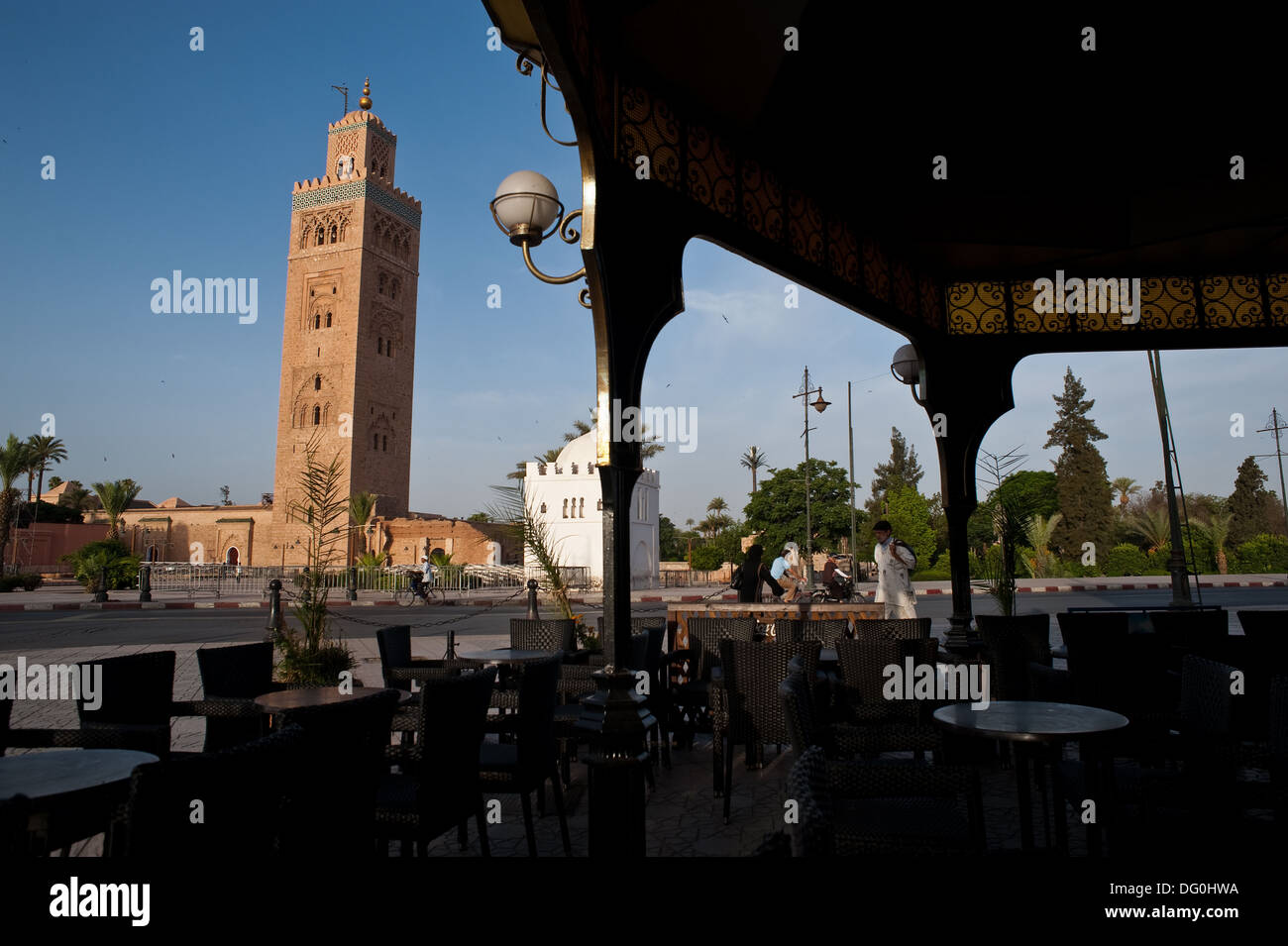 The minaret of the Koutoubia mosque. In the foreground, the deserted terrace of a café during the month of - Stock Image