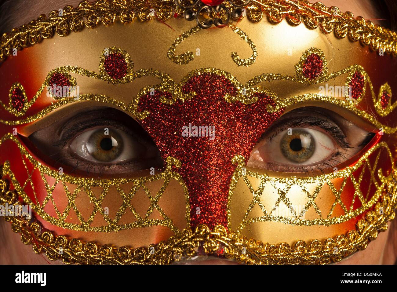 Wide opened eyes of a woman behind a venetian mask - Stock Image