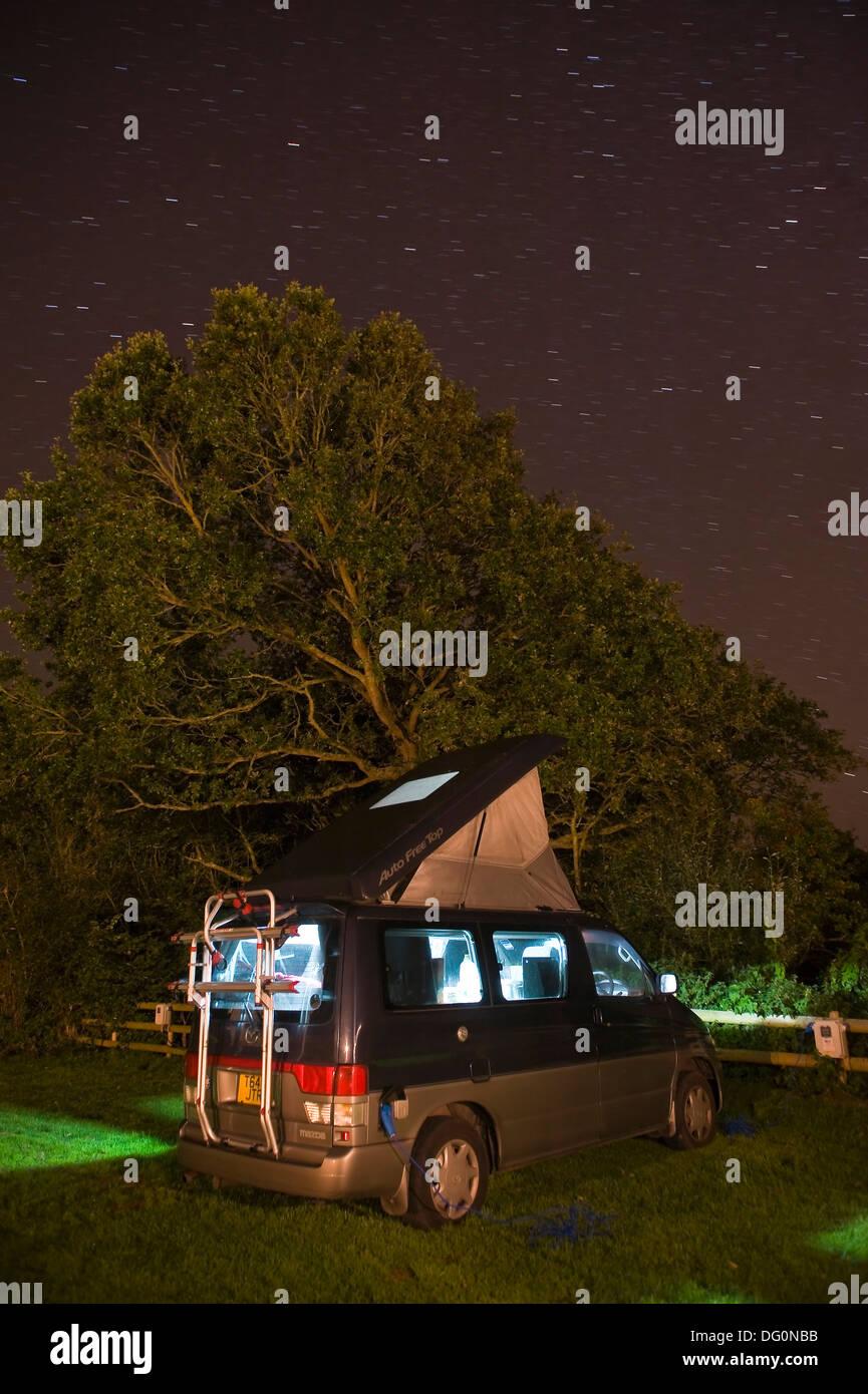 Moving stars in the night sky above a camper van in Dorset, UK - Stock Image