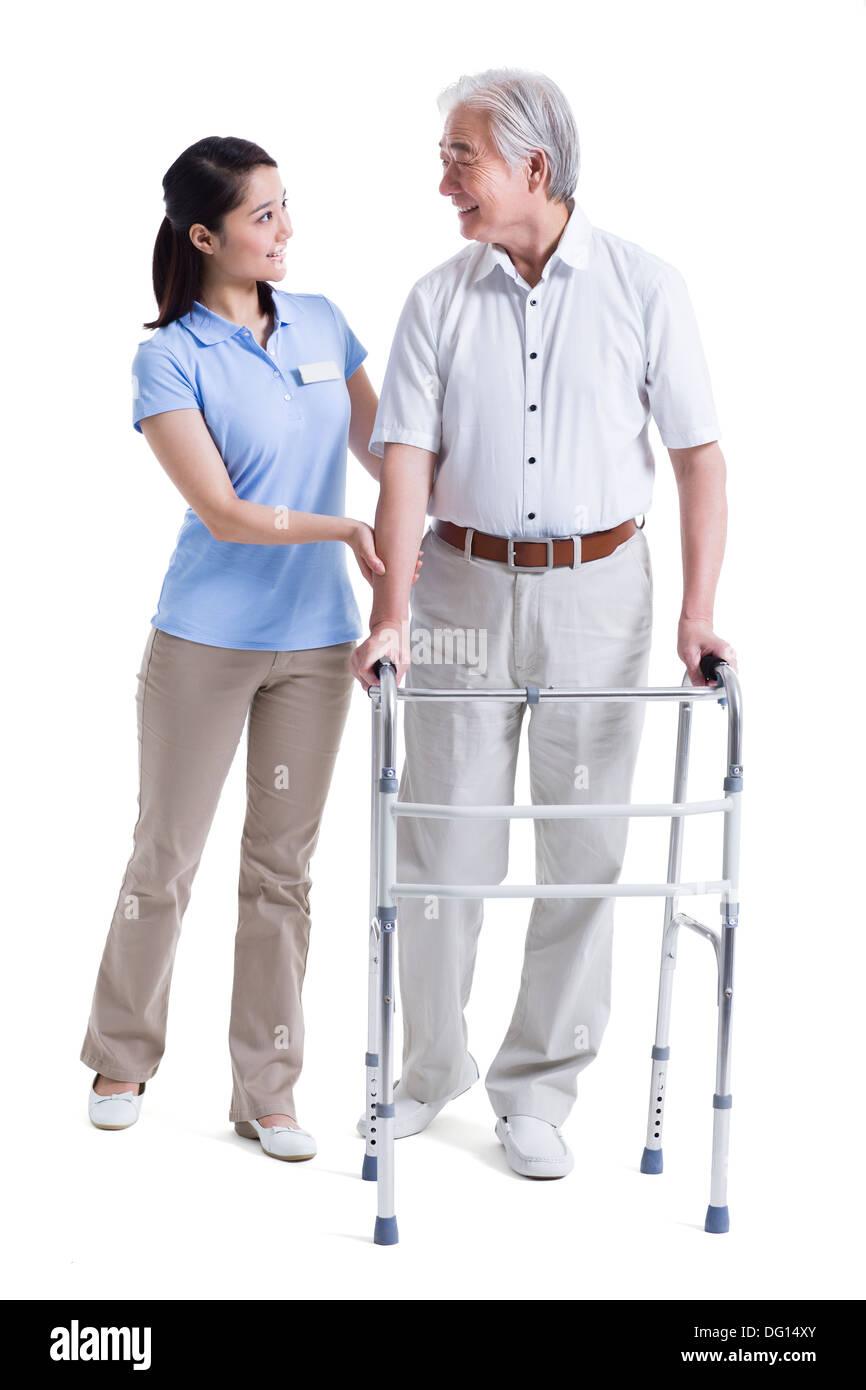 Female nursing assistant helping senior man with walking frame - Stock Image