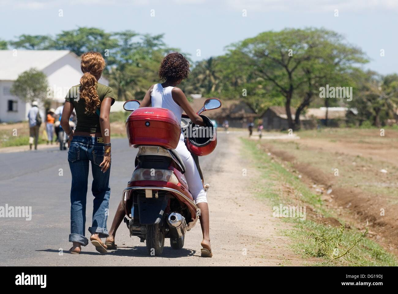 young girls riding scooter, Hell-Ville Andoany, Nosy Be island, Republic of Madagascar, Indian Ocean - Stock Image