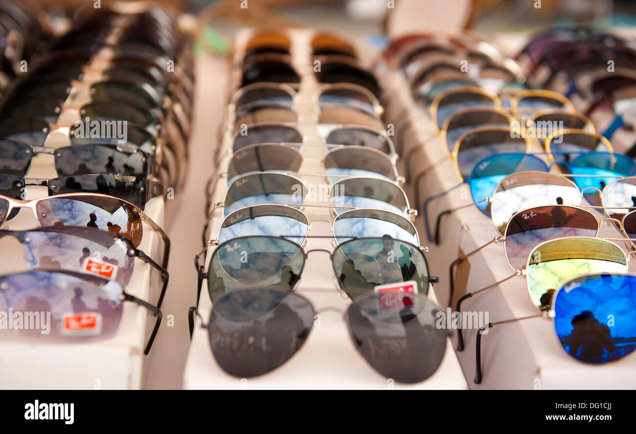 Rows of sunglasses on outdoor market stall - Stock Image