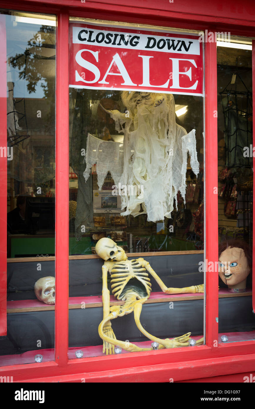 A shop window with closing down sale sign in the window and a joke skeleton on display - Stock Image