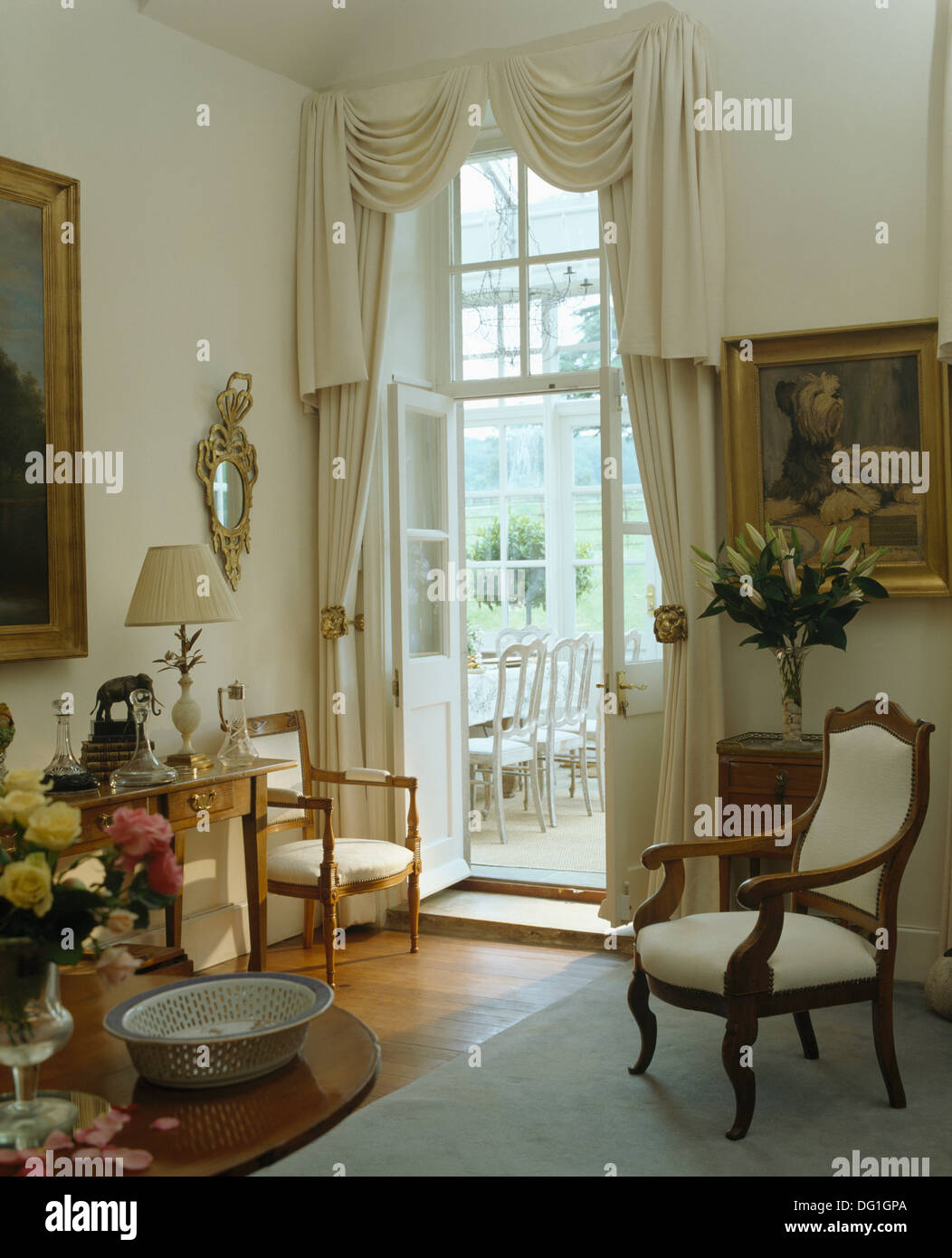 Cream Upholstered Chair In Country Drawing Room With Cream Curtains On  French Windows To Dining Room