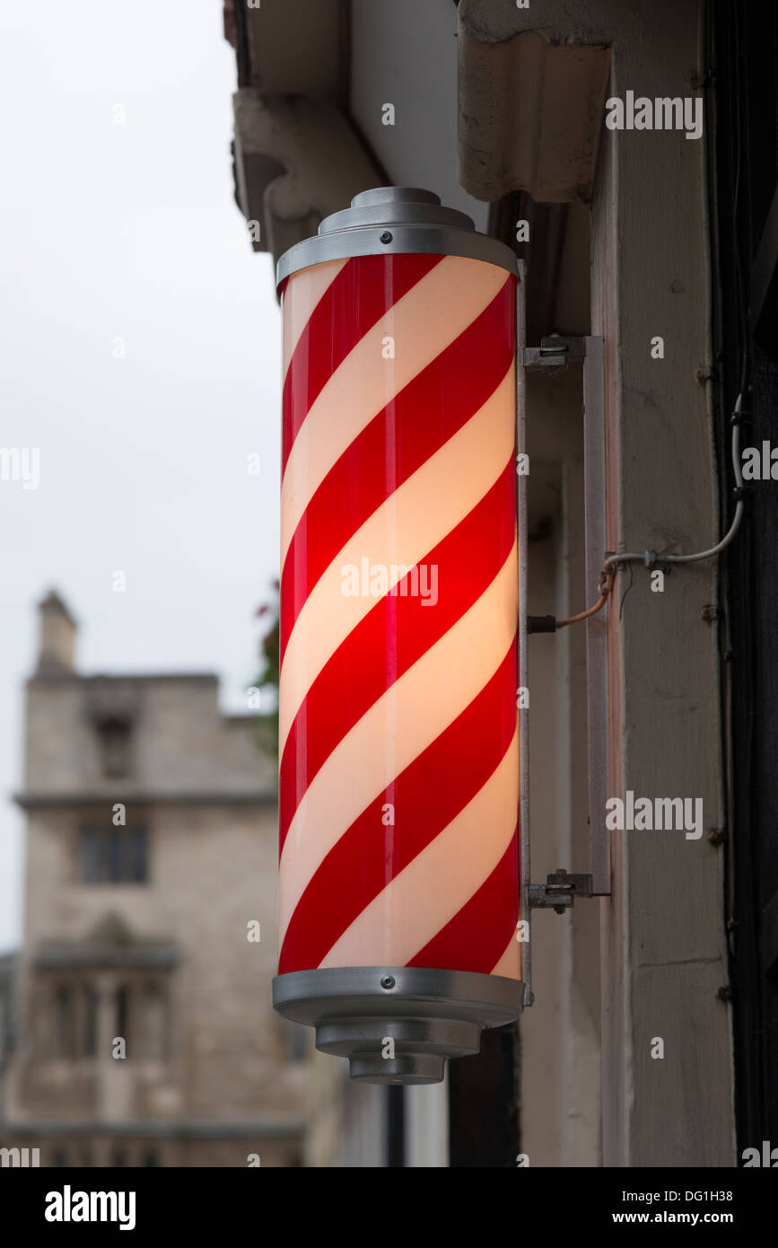 a barber's red and white striped pole outside a shop in Cambridge UK - Stock Image