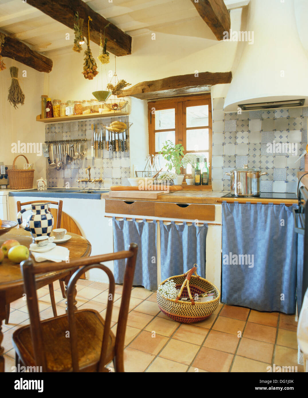 Blue Curtains On Cupboards In French Country Kitchen With Terracotta Stock Photo Alamy