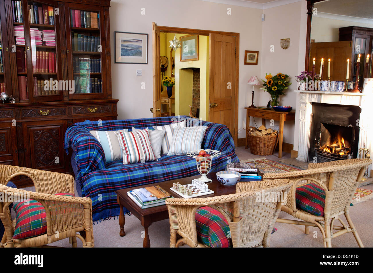 Blue plaid throw on sofa with wicker chairs in country ...