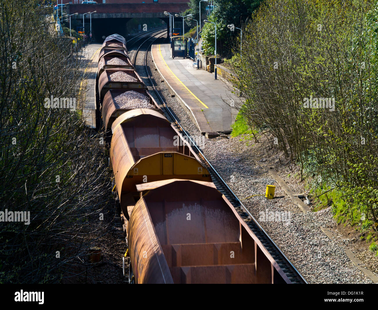 View looking down on goods train carrying freight including quarry stone through Belper railway station Derbyshire England UK - Stock Image