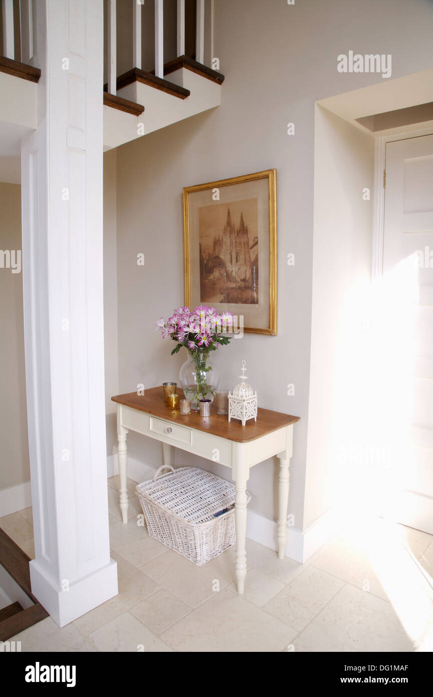 Picture On Wall Above White Painted Console Table And Wicker Basket In  White Country Hall