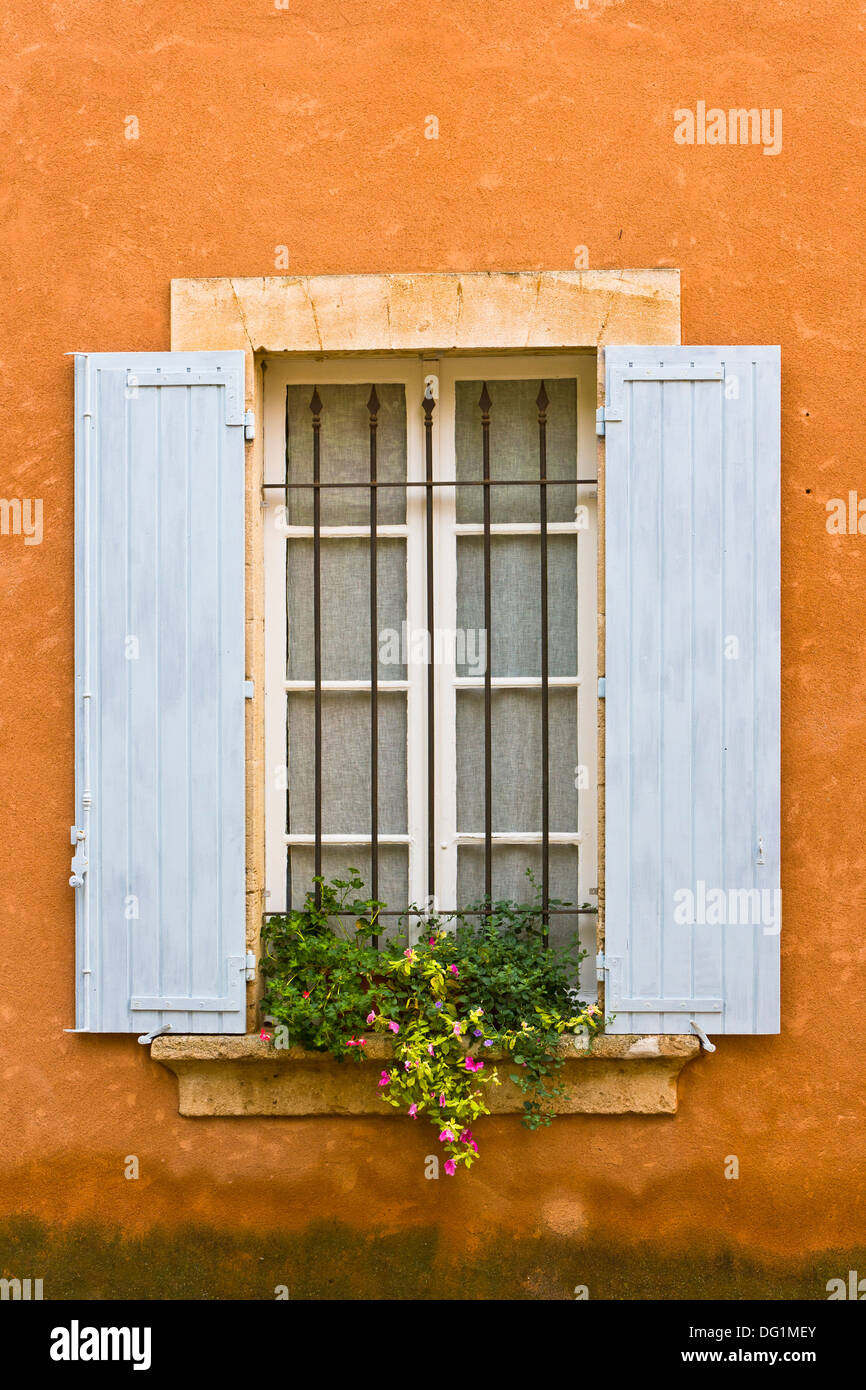 Close up of blue window shutters with a flower box in Provence, France, Europe - Stock Image