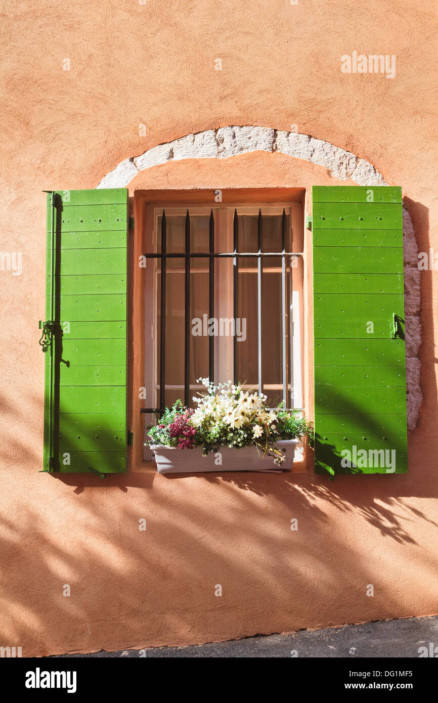 Close up of green window shutters with a flower box in Provence, France, Europe - Stock Image