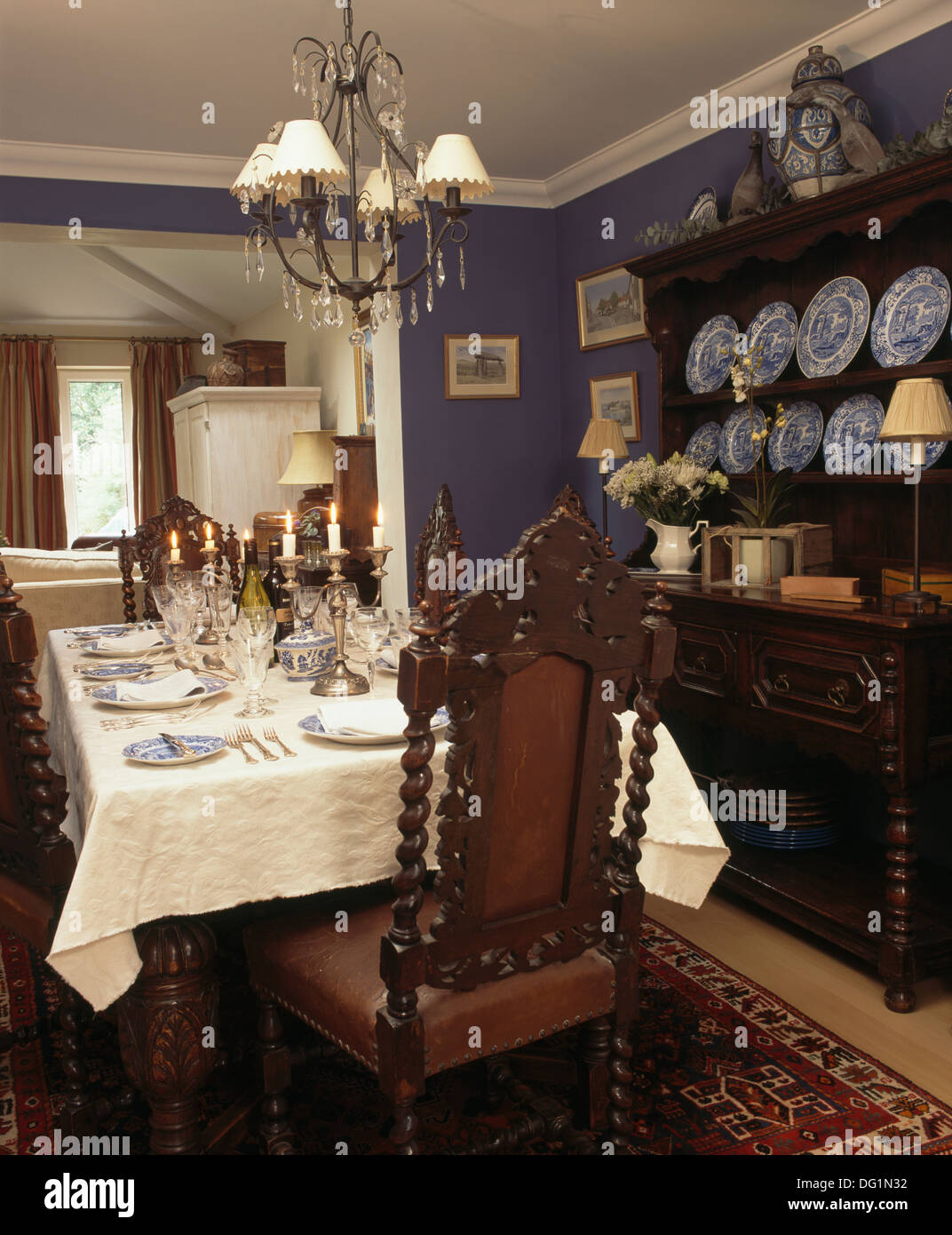 Antique Jacobean style chairs and oak dresser in blue dining room with chandelier above table with white cloth laid Stock Photo