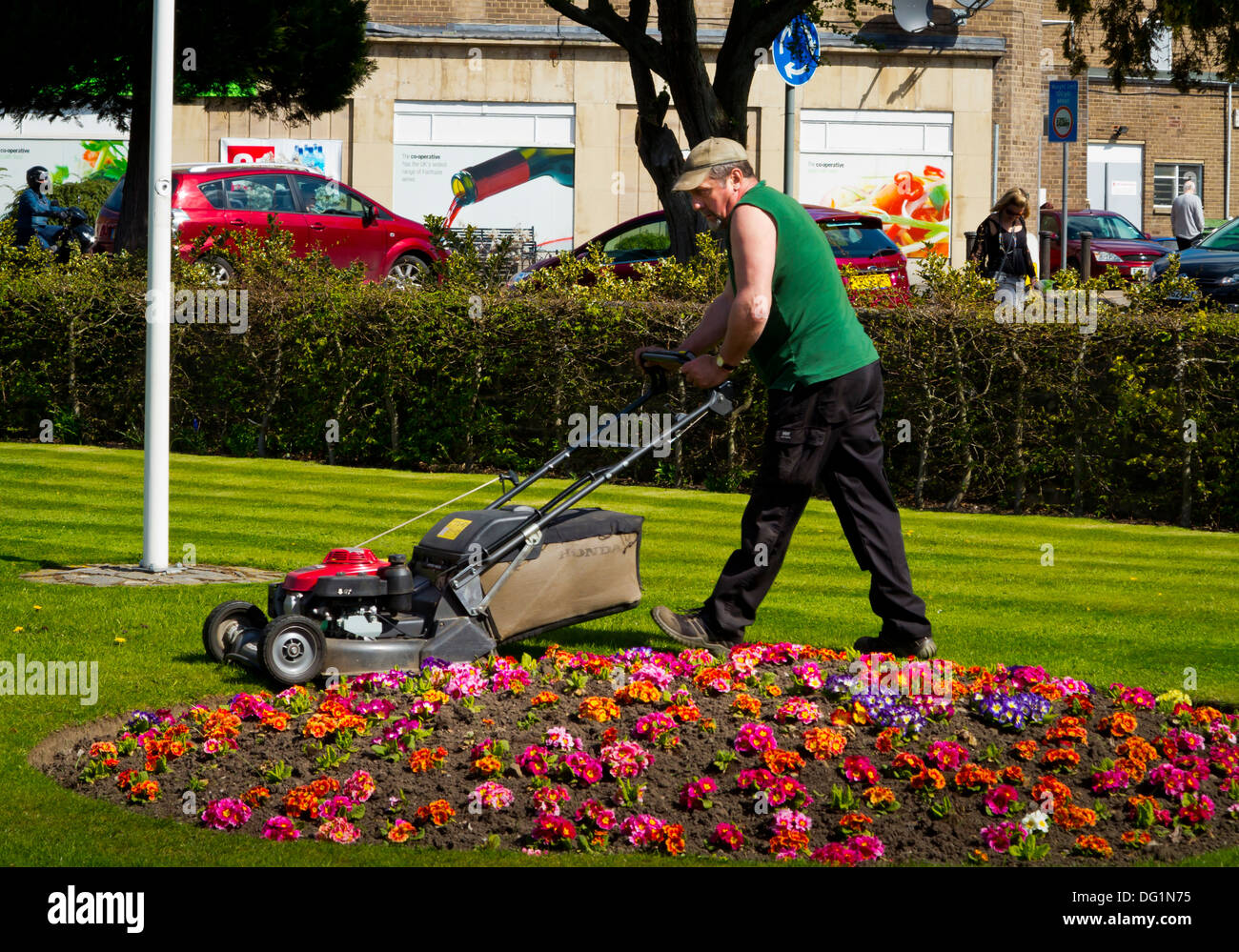 Council gardener mowing lawn in Hall Leys Park in Matlock Derbyshire England UK an award winning park in the Peak District - Stock Image